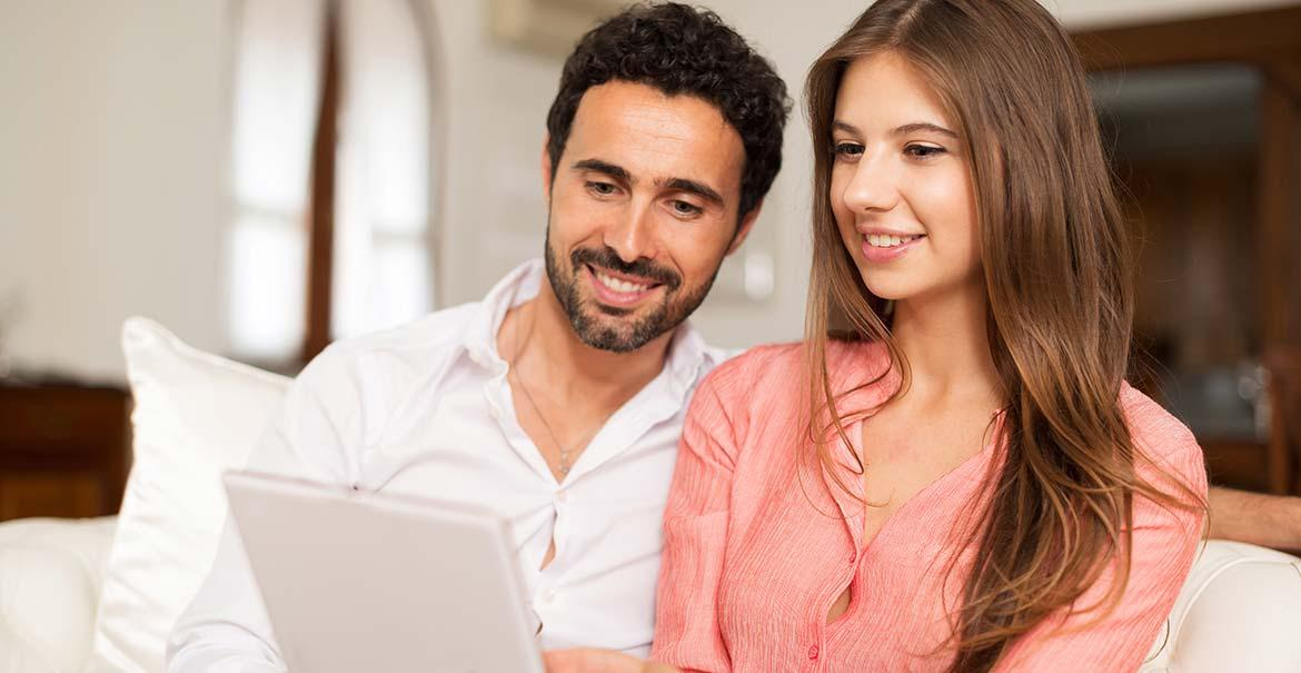 A happy couple looking at a laptop